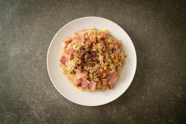 Arroz frito com presunto de bacon e pimentão preto em prato branco