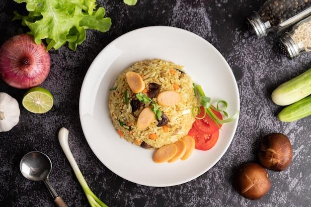 Arroz frito com salsicha com tomate, cenoura e cogumelos shiitake no prato