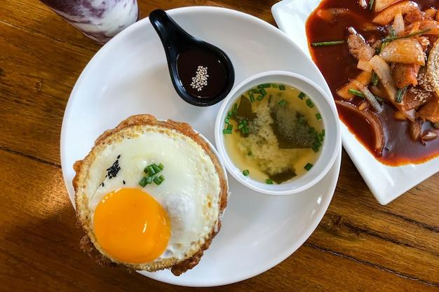 Arroz frito kimchi com ovo frito e carne de porco. estilo de comida coreana.