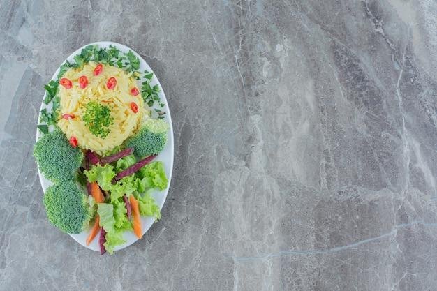 Arroz integral cozido servido com pimenta picada, repolho, verduras, cenoura e pedaços de brócolis em uma travessa sobre mármore.