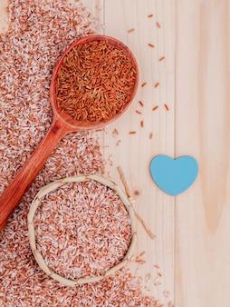 Arroz integral da grão para o alimento saudável e limpo no fundo de madeira.