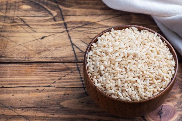Arroz integral de grãos longos crus em uma tigela, espaço de cópia de madeira