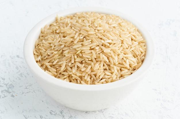 Arroz integral em uma tigela branca em branco. cereais secos em copo, comida vegan