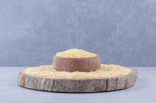 Arroz integral empilhado em uma fatia de tora com uma tigela cheia no meio, sobre uma superfície de mármore