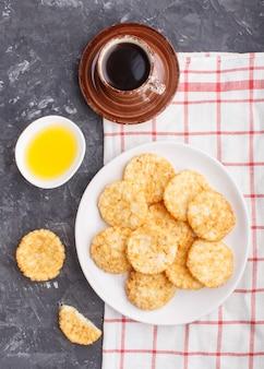 Arroz japonês tradicional chips de cookies com molho de mel e soja em um prato de cerâmico branco e uma xícara de café
