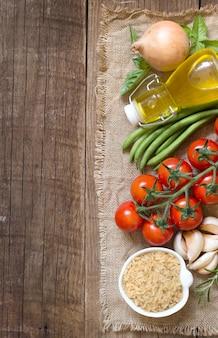 Arroz não polido seco, azeite, legumes e ervas em uma vista superior de mesa de madeira com espaço de cópia
