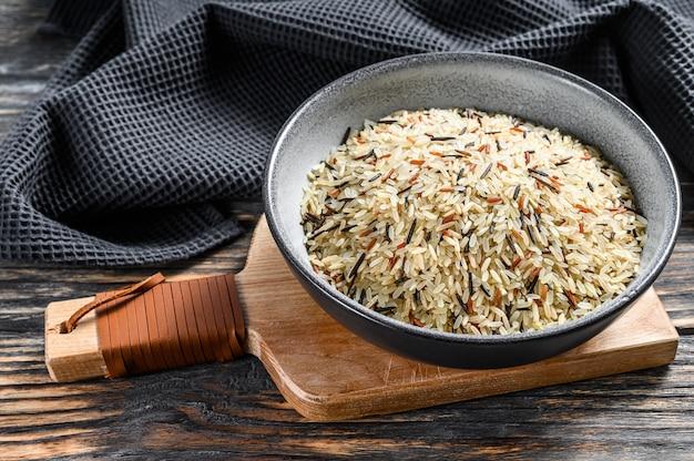 Arroz orgânico, arroz misturado em uma tigela. fundo preto. vista do topo