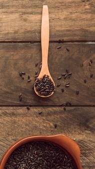 Arroz orgânico marrom na colher de pau e tigela na mesa de madeira