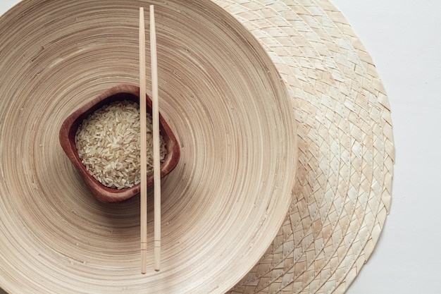 Arroz parboilizado em tigela de madeira com pauzinhos de madeira
