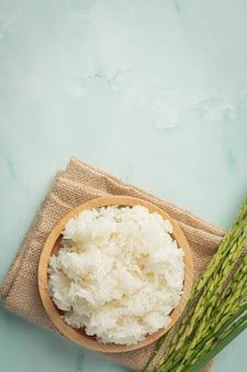 Arroz pegajoso com planta de arroz colocado em tecido marrom