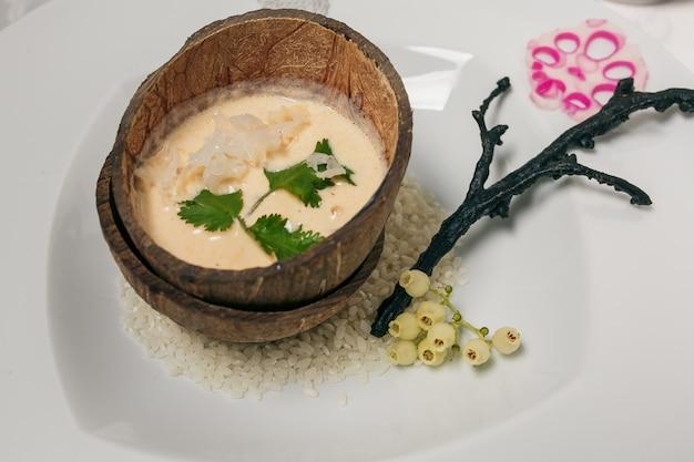 Arroz pegajoso marrom cozinhado no escudo do coco, alimento tradicional tailandês.