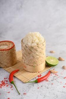 Arroz pegajoso tailandês em uma cesta de bambu tecida em um painel de madeira com pimentões, limão e alho