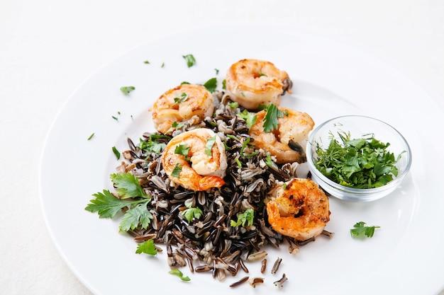 Arroz preto com camarão no prato branco