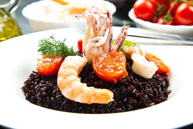Arroz preto com lulas fatiadas, camarão e tomate na chapa branca