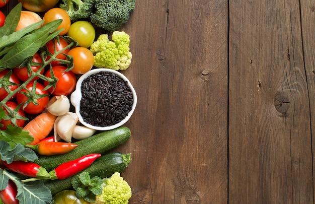 Arroz preto cru em uma tigela com legumes na madeira