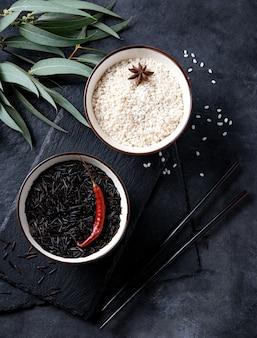 Arroz preto e branco em duas tigela azul com pimenta vermelha e anice em uma placa de ardósia em um fundo preto