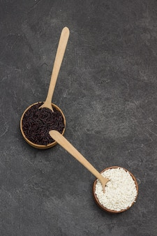 Arroz preto e branco em uma tigela de madeira. colheres de madeira em uma tigela. postura plana.