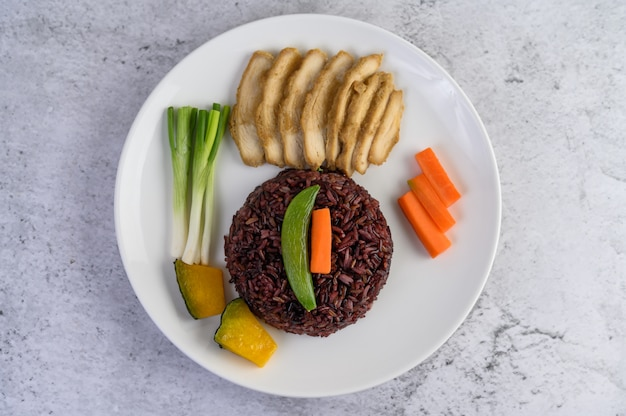 Arroz preto em um prato com abóbora, ervilhas, cenouras, milho e peito de frango cozido no vapor.