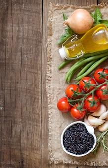 Arroz preto seco, azeite, legumes e ervas em uma vista superior de mesa de madeira com espaço de cópia