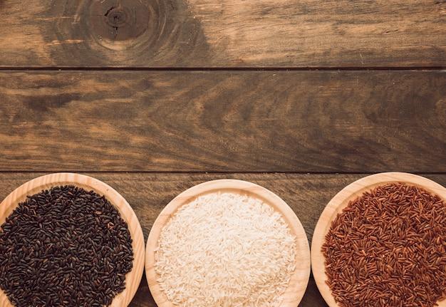 Arroz preto vermelho; arroz branco e tigelas de grãos de arroz vermelho jasmim na mesa de madeira