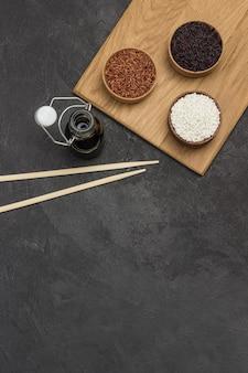 Arroz preto, vermelho e branco em tigelas de madeira. molho de soja em frasco de vidro. varas de bambu. postura plana.