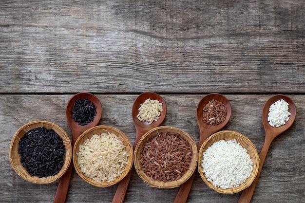 Arroz, riceberry, arroz integral de jasmim, arroz integral vermelho de jasmim em uma superfície de madeira velha. vista superior, plana leigos.