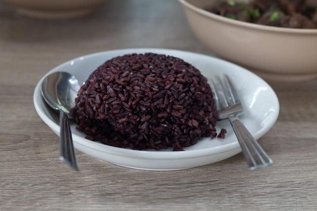 Arroz roxo cozido no prato branco pronto para servir
