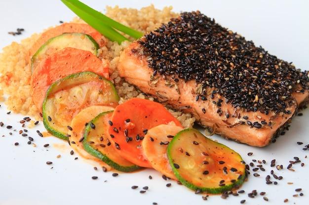 Arroz, salmão e vegetais decorados com sementes de chia servidos em um prato branco