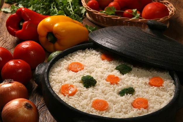 Arroz saudável apetitoso com legumes em chapa branca sobre uma mesa de madeira. arroz colorido
