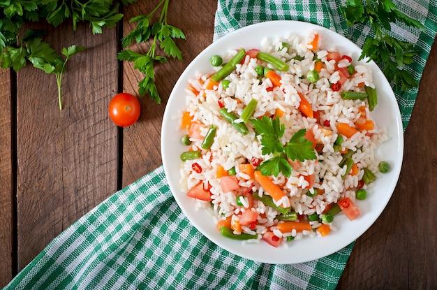 Arroz saudável apetitoso com legumes em chapa branca sobre uma mesa de madeira