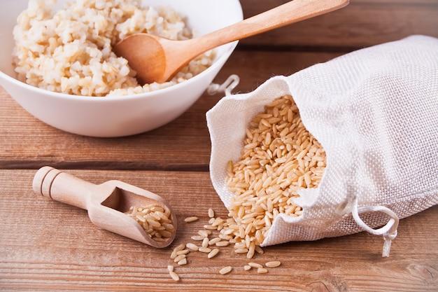 Arroz seco em um saco e arroz integral cozido em uma tigela branca na madeira
