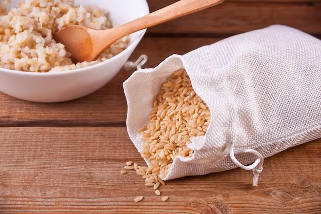 Arroz seco em um saco e arroz integral cozinhado na bacia branca no fundo de madeira.