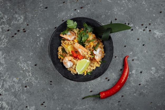 Arroz tailandês com camarão em prato preto
