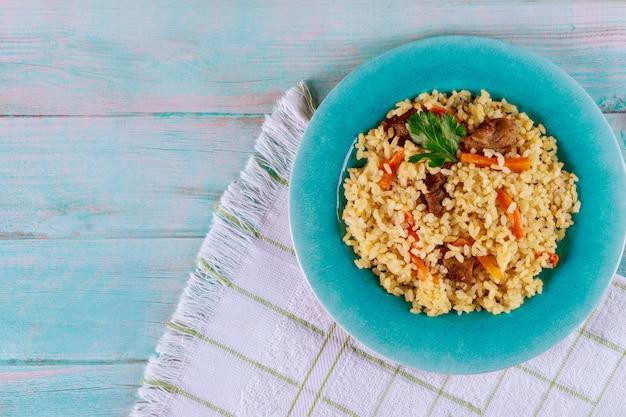 Arroz tailandês com carne e vegetais no prato azul.