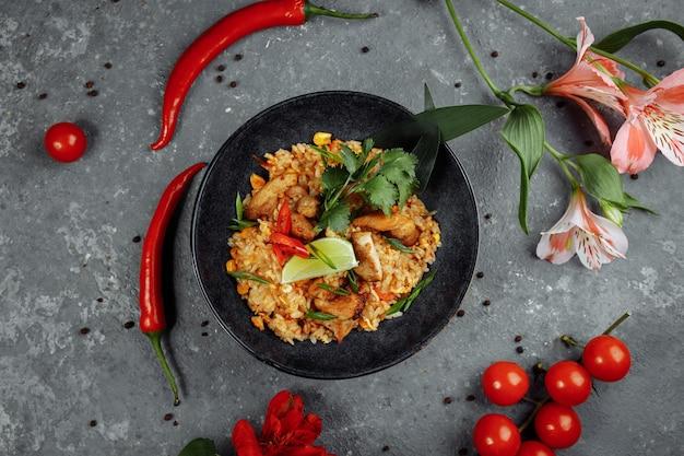 Arroz tailandês com frango. prato tailandês de arroz, frango, cebola yalta, milho, abacaxi, tomate, molho de soja, pasta de pimentão, coentro, limão, pimenta pimentão especiarias cebola verde