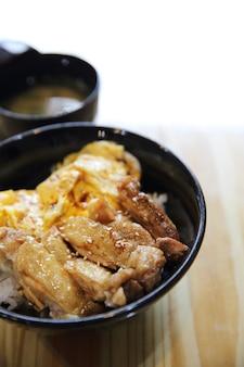 Arroz teriyaki de frango grelhado e ovo em fundo de madeira