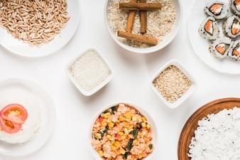 Arroz tufado; arroz frito chinês; arroz cru com paus de canela e sushi no fundo branco