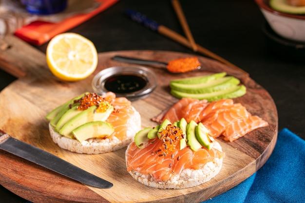 Arroz tufado com salmão cru e abacate em uma mesa escura