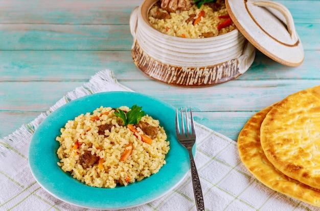 Arroz uzbeque com carne, cenoura e alho em panela de barro