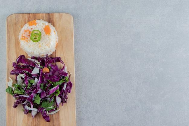 Arroz vegetariano com legumes a bordo, no fundo de mármore.