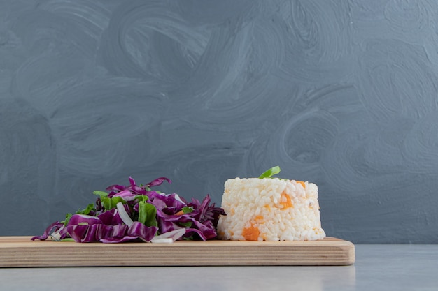 Arroz vegetariano com legumes a bordo, no mármore.