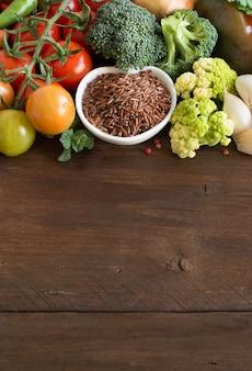 Arroz vermelho cru em uma tigela com legumes na madeira