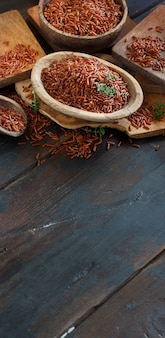 Arroz vermelho cru em uma tigela com uma colher de pau na mesa