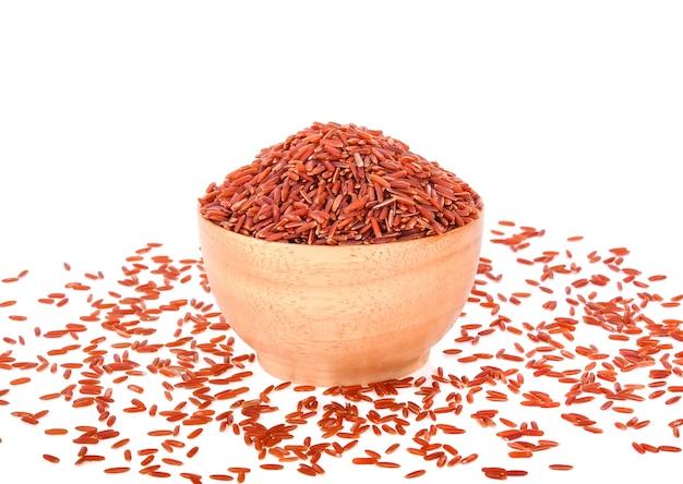 Arroz vermelho em uma tigela de madeira, isolado no fundo branco