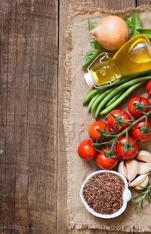 Arroz vermelho seco, azeite, legumes e ervas em uma vista superior de mesa de madeira com espaço de cópia