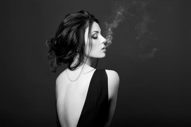Art morena mulher fumando em um fundo escuro de vestido preto. retrato clássico de mulher forte e confiante