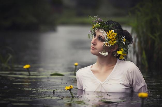 Art mulher com coroa de flores na cabeça em um pântano