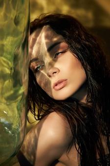 Art portrait de uma mulher de maquiagem com reflexo da luz do sol no rosto, refração da luz através de uma grande garrafa de vidro. menina sentada no chão em uma parede amarela