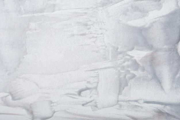 Arte abstrata fundo cinza claro e cores brancas. pintura em aquarela sobre tela com pinceladas de prata e salpicos. arte em acrílico sobre papel com padrão de pinceladas. cenário de pedra.