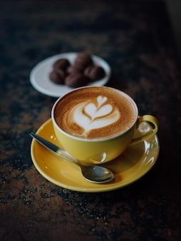 Arte amarela do latte da chávena de café no café da cafetaria